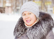 Beautiful woman in a coat with fur collar and a knitted hat
