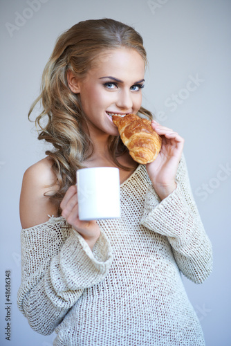 Woman enjoying a fresh crispy croissant