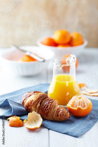 Croissant, mandarins and mandarin juice on kitchen table