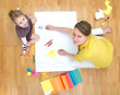 Young woman and little girl drawing. Top view.