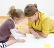 Young woman and little girl drawing together