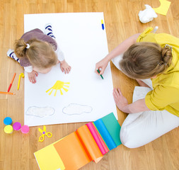 Young woman and little girl drawing. Top view