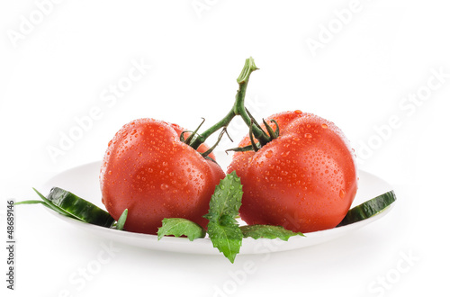Tomatoes and basil on white plate, isolated on white background