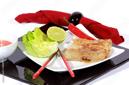 crispy springrolls on dish with salad isolated on the white