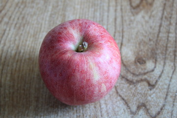 A single red apple displayed on a table
