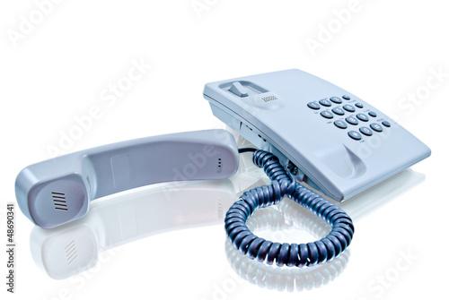 Стационарный телефон на белом фоне с отражением
