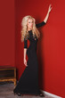 Fashion model in long black dress in glamorous red interior