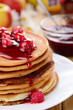 Delicious pancakes with raspberries on the wooden kitchen  tabl