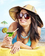 Girl in bikini drinking alcohol coctail through a straw.
