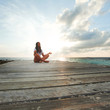 Yoga woman meditating near sea