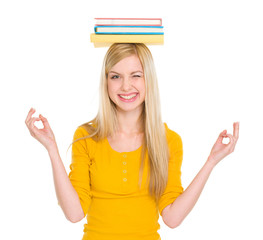 Student girl in yoga pose with books on head