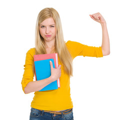 Happy student girl with book showing biceps