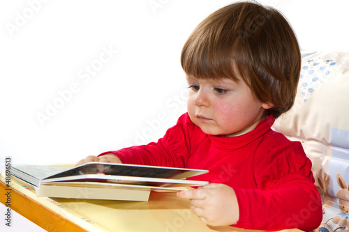 adorable one-year old baby reading a book