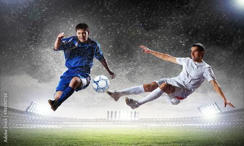 dwóch piłkarzy uderzając piłkę
