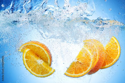 Orange Slices falling deeply under water with a big splash