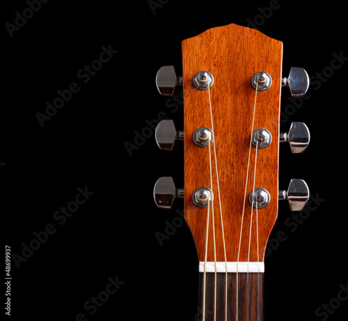 Top of guitar neck over black background