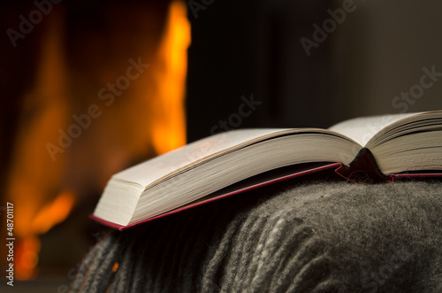 Peaceful and warm closeup of a open book by fireplace.
