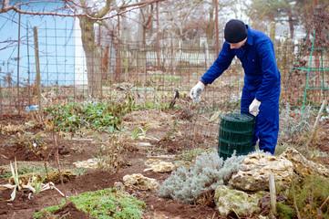 Gardener unwrapping metallic wire mesh