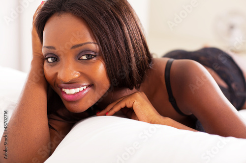 pretty african american woman lying on bed