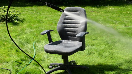 office chair cleaning under strong water stream on  green grass