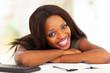 happy african american university student lying on desk
