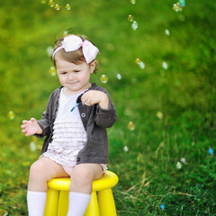 Little girl with bubble blower in a park