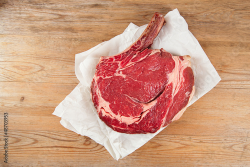 Bone-in Rib eye Steak steak on paper and wooden table
