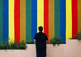 YOUNG MAN IN FRONT OF THE COLORFUL WALL