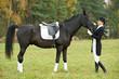woman jockey in uniform with horse