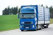 Blue lorry with trailer over blue sky