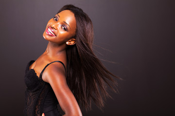 pretty african american woman with long hair on black background