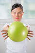 Portrait of fit and healthy gym woman with ball at fitness club