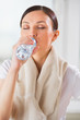 Portrait of young woman drinking water at gym after doing exerci