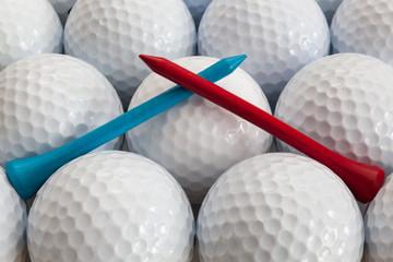 An closeup of a regular a blue and red golf tees on a golf balls