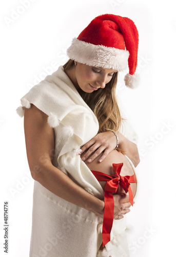 Smiling pregnant woman wearing santa hat isolated over white