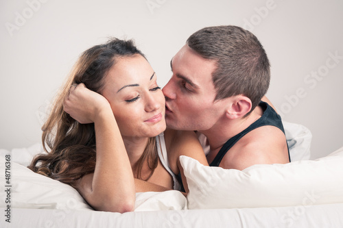 Happy young couple close up portrait in a romantic mood in bedro