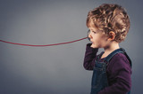 Young kid listen to tin can telephone.