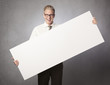 Joyful businessman presenting white blank billboard.