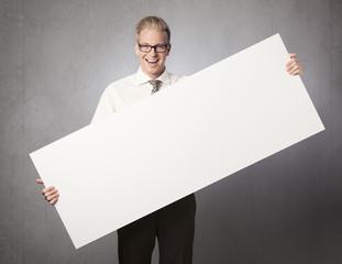 Joyful businessman presenting white blank billboard.
