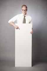 Friendly businessman pointing finger at blank vertical billboard