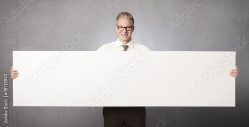 Smiling businessman showing white empty panel.