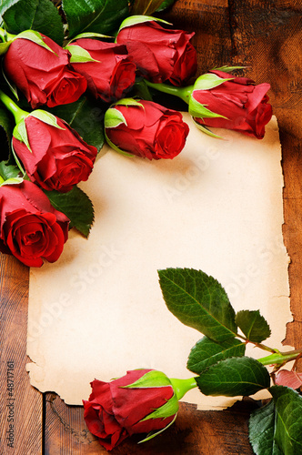 Frame with red roses and vintage paper