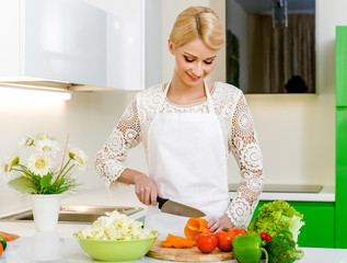 Smiling young woman preparing vegetarian salad