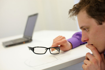 thinking man holding eyeglasses - notebook in background
