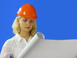woman architect wearing a hardhat examining blueprints