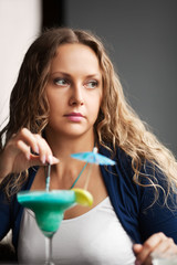 Sad young woman with cocktail at a restaurant