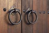 Old medieval metal handles on antique dark wooden door