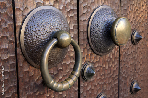 Medieval metal handle and doorknob on a wooden door