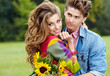 Young couple with sunflowers, outdoors