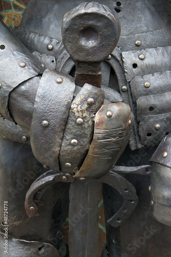 Medieval iron knight holding metal sword